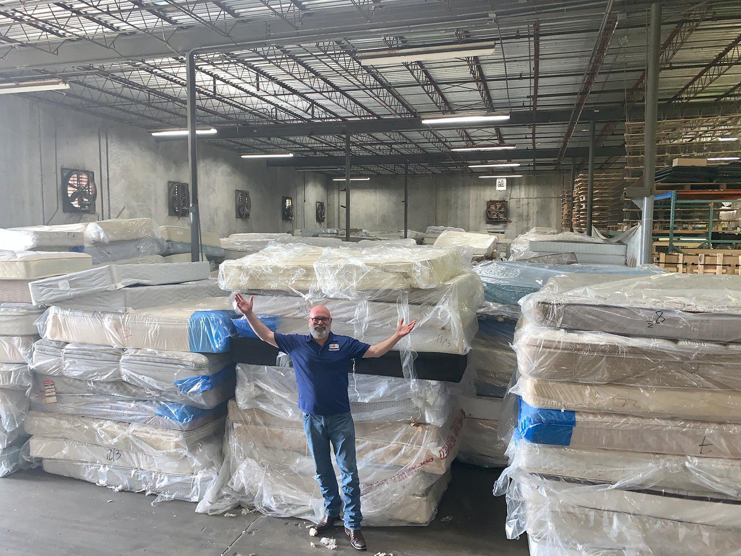 Board Chairman Hal Lynde stands in front of a mountain of mattresses for recycling
